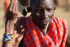 Man poking knife through hole in earlobe. A man pokes a long knife through a hole in a Masai tribesman's earlobe. He has a stick in his mouth as a toothbrush and royalty free stock image