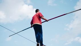 A man with a pole is on a cable above the ground. stock footage