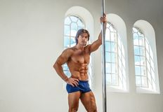 Man pole dancing in a hall with big windows. Abdominal shirtless male pole dancing in a big hall with light windows Royalty Free Stock Photography