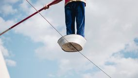 A man with a pole in his hands jumping on the rope. Dangerous stunt above the ground. stock video footage
