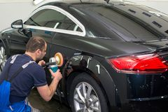 A man polishes a black car. With a polisher Royalty Free Stock Photography