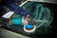 MAn polishes the front glass. Close-up of a male mechanic with a blue prism and protective gloves polishes the front glass of the car with a polishing machine Stock Photos