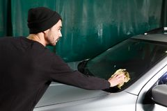 A man polishes a front glass royalty free stock image