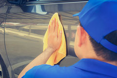 A man polishing car with microfiber cloth Royalty Free Stock Images
