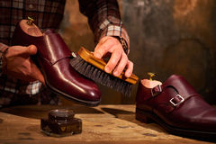 Man polishing leather shoes with brush. Stock Image