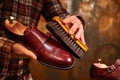 Man polishing leather shoes with brush. Royalty Free Stock Photo