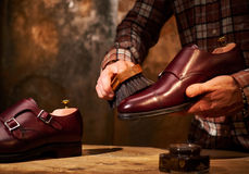 Man polishing leather shoes with brush Stock Photos