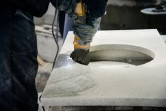 Man polishing marble stone table by small angle grinder stock photography