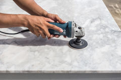 Man polishing marble table by angle grinder Royalty Free Stock Photo