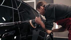Man polishing new black car. Creating perfect glance. stock video