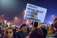 Man with political slogan at Bucharest demonstrations. An old man with the sign saying Announcement! We have awoken and are searching for competent leaders! at Stock Photo