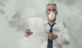 Man with pollution mask holding a sign Royalty Free Stock Photography