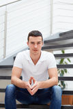 Man in a polo shirt is sitting on the stairs Stock Photos