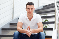 Man in a polo shirt is sitting on the stairs Royalty Free Stock Photo