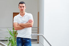 Man in a polo shirt stands leaning on railing Stock Photography