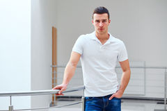 Man in a polo shirt stands leaning on railing Royalty Free Stock Photography