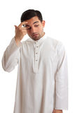 Man pondering or contemplating a decision. Middle eastern ethnic man wearing a robe, kurta, dishdash, thoub, etc held together with ruby inset buttons.  He is Royalty Free Stock Photos