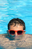Man in pool. Young man diving into a pool with red sunglasses. He takes half a head above the water Royalty Free Stock Photography