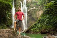 Man in pool at the base of large waterfall. Man enjoying pool at the base of large waterfall in Hawaii Royalty Free Stock Photography