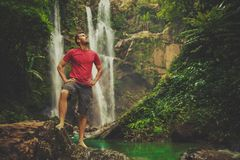 Man in pool at the base of large waterfall. Man enjoying pool at the base of large waterfall in Hawaii Royalty Free Stock Images