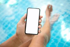 Man at the pool holding phone with an isolated screen Royalty Free Stock Images