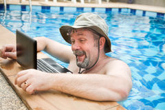 Man in pool with laptop Stock Photos