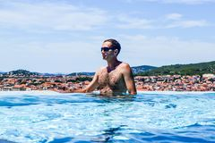 The man in the pool. Against the backdrop of the sea and islands stock images