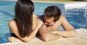 Man in pool standing with girlfriend kisses her stock video footage