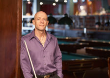 Man with pool stick. Confident handsome man with pool stick at billiards nightclub Stock Photography