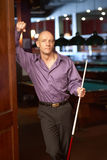 Man with pool stick billiards Royalty Free Stock Image