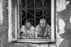 A man in a poor quarter looking out the window of an old house. Barnaul,Russia-may 1, 2019. A man in a poor quarter looking out the window of an old house stock photo