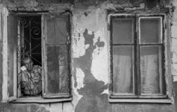 A man in a poor quarter looking out the window of an old house. Barnaul,Russia-may 1, 2019. A man in a poor quarter looking out the window of an old house stock image