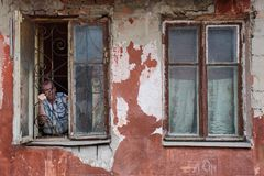 A man in a poor quarter looking out the window of an old house. Barnaul,Russia-may 1, 2019. A man in a poor quarter looking out the window of an old house royalty free stock photography