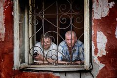 A man in a poor quarter looking out the window of an old house. Barnaul,Russia-may 1, 2019. A man in a poor quarter looking out the window of an old house royalty free stock photos