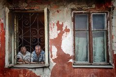 A man in a poor quarter looking out the window of an old house. Barnaul,Russia-may 1, 2019. A man in a poor quarter looking out the window of an old house royalty free stock photo
