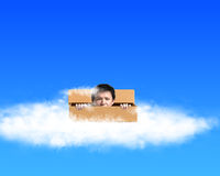 Man pop out his head outside the box on the clouds in sky backgr Stock Images