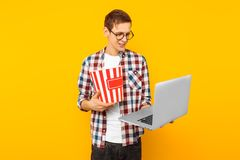 A man with popcorn and a laptop on a yellow background stock image
