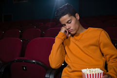 Man with popcorn sleeping in theatre. Bored man with popcorn sleeping in theatre Stock Photos