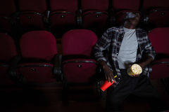 Man with popcorn sleeping in theatre. Bored man with popcorn sleeping in theatre Royalty Free Stock Image