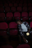 Man with popcorn sleeping in theatre. Bored man with popcorn sleeping in theatre Royalty Free Stock Photography