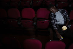 Man with popcorn sleeping in theatre. Bored man with popcorn sleeping in theatre Stock Images