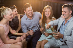 Man popping a champagne bottle while friends watching him stock photos