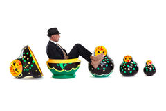 Man popping out of a set of painted Russian nesting dolls Stock Images