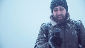 Man with portable radio ser searching signal. Cold man holding portable radio set and trying to catch a signal in blizzard try to call help, middle 4K shot stock video