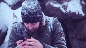 Man with portable radio ser searching signal. Cold man holding portable radio set and trying to catch a signal in blizzard try to call help, middle 4K shot stock footage