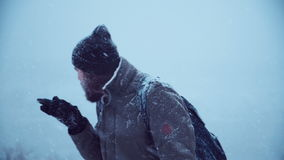 Man with portable radio ser searching signal. Cold man holding portable radio set and trying to catch a signal in blizzard try to call help, middle shot stock footage
