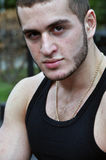 Man portrait. This is a close up portrait of a young man with a calm, yet serious expression. He is facing the camera and wearing a tank top Stock Image