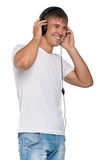 Man portrait. Portrait of relaxed young man listening to music on headphone against isolated on white background Royalty Free Stock Images