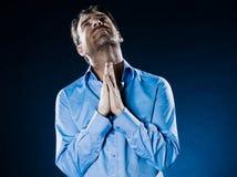 Man Portrait Despair Beg. Caucasian man unshaven praying portrait isolated studio on black background Stock Photo
