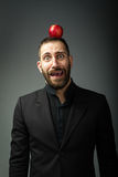 Man portrait in gray background with apple on head Royalty Free Stock Image